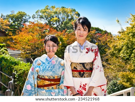 KYOTO - OCT 24,2014: Two japanese women with traditional kimono in fall park on Oct 24, 2014,Kyoto, Japan. Viewing the fall foliage is a cultural pastime in Japan dating from antiquity. - stock photo