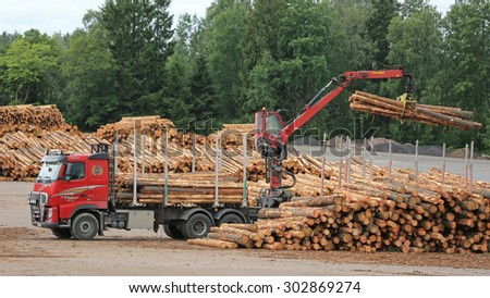 KYRO, FINLAND - AUGUST 1, 2015: Volvo FH and Hiab crane unload pine logs at mill lumber yard. The investments of the Finnish forest industry will increase by 50 percent in 2015.
