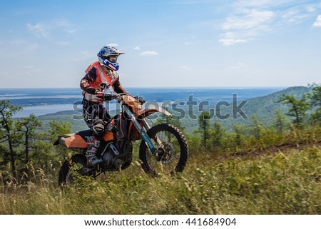 Kyshtym, Russia - June 19, 2016: athlete motorcyclist riding on mountain in background of mountains and lake during Ural Cup in Enduro