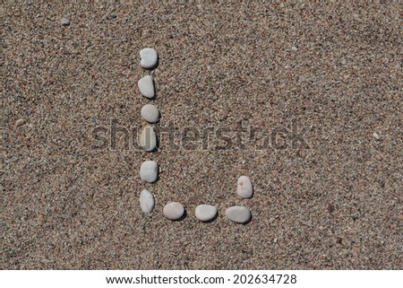 L letter made of stones on sand  - stock photo