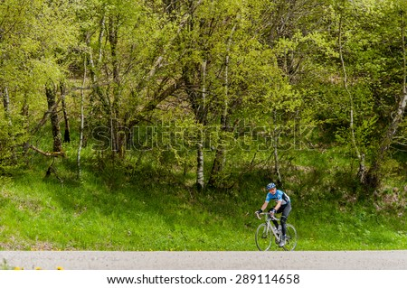 LA BRESSE, FRANCE - MAY 18, 2013: A man on a road racing bicycle in training on a steep road in the Vosges mountains. - stock photo
