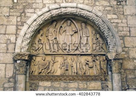 LA CHARITE SUR LOIRE, FRANCE -AUGUST 1, 2005: The decoration of the facade of the church Sainte-Croix-Notre-Dame. Church was listed as a UNESCO WH Site, as part of the Routes of Santiago de Compostela - stock photo