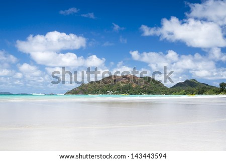 La Digue island, Seyshelles, Anse Source d'Argent. White coral beach sand. Sailing yacht on background. - stock photo