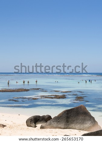 La Digue - November 8, 2014: Tourists bathe on a beautiful beach with coral sand and huge rocks at low tide on a clear day on the shores of the Indian Ocean November 8, 2014, La Digue, Seychelles - stock photo