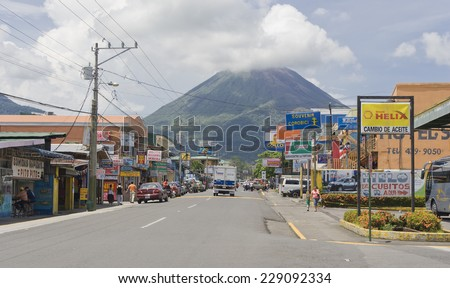 LA FORTUNA, COSTA RICA - SEPTEMBER 27, 2008: Main street with cars, shops and pedestrians in La Fortuna, Costa Rica. In the background the active Volcano Arenal in the Arenal Volcano National Park. - stock photo