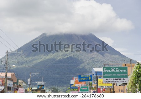 LA FORTUNA, COSTA RICA - SEPTEMBER 27, 2008: Volcano Arenal behind power cables and signs in La Fortuna, Costa Rica. Volcano Arenal is one of the most active volcanos in the world. - stock photo