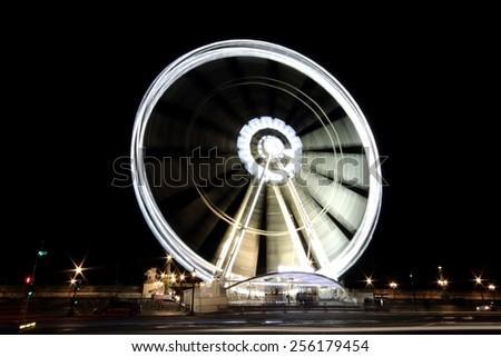 La Grand Roue de Paris by night, a transportable Ferris wheel originally installed on the Place de la Concorde in Paris, France. Long exposure. - stock photo