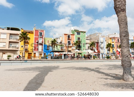 LA JOIOSA, SPAIN - SEPTEMBER 1; Long shadows of palm trees on sand in front of multi-colored homes on September 1, 2016,  La Vila Joiosa, Costa Blanca Spain.