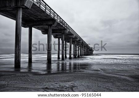 La Jolla beach, California,  long exposure under the pylons, black and white image. - stock photo