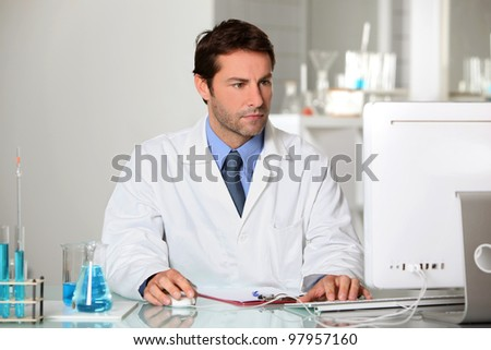 Lab technician studying test results on a computer - stock photo