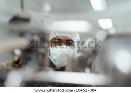 Lab technician working as researcher in biotechnology plant with machinery - stock photo