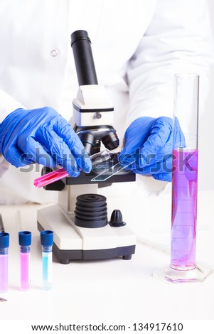 Lab technician working with equipment: tweezers, microscope, test tubes  filled with colored fluid, chemical flasks - stock photo