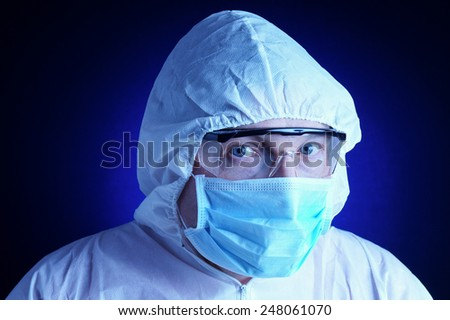 Lab worker in protective suit and blue background - stock photo