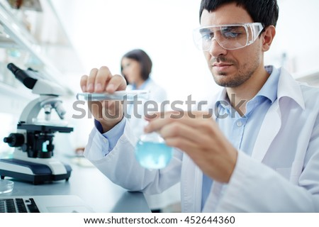 Lab worker in uniform testing new substance - stock photo