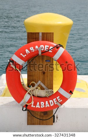 LABADEE, HAITI - SEPTEMBER 27, 2015:  Labadee, Haiti Photo Op on the Dock with an orange Life Ring next to a Hitching Post for Cruise Ships and Boats to tie to the dock. - stock photo