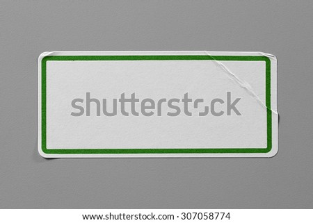 Label Adhesive Close Up on Grey Background with Real Shadow. Top View of Adhesive Paper Tag with Green Border. Stickers with Copy Space for Text or Image