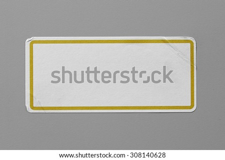 Label Adhesive Close Up on Grey Background with Real Shadow. Top View of Adhesive Paper Tag with Yellow Border. Stickers with Copy Space for Text or Image - stock photo