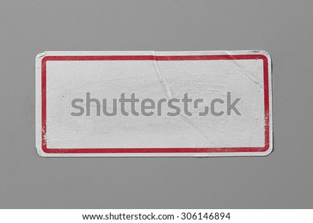 Label Adhesive with Dirt and Scratches Close Up on Grey Background with Real Shadow. Top View of Adhesive Paper Tag with Red Border. Stickers with Copy Space for Text or Image - stock photo