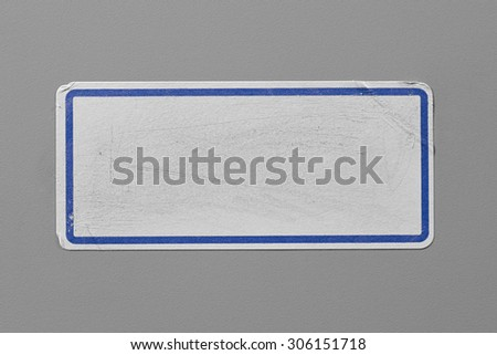 Label Adhesive with Dirt and Scratches Close Up on Grey Background with Real Shadow. Top View of Adhesive Paper Tag with Blue Border. Stickers with Copy Space for Text or Image - stock photo