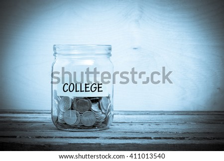 Label on a glass jar with the inscription - college. Glass jar with coins. Financial concept on wooden background - stock photo
