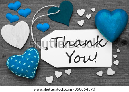 Label With Blue Textile Hearts On Wooden Gray Background. English Text Thank You. Retro Or Vintage Style. Black And White Image With Colored Hot Spot. - stock photo