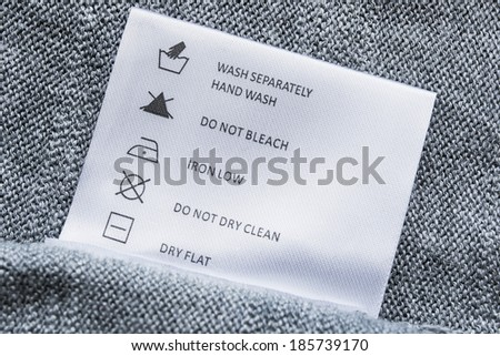 Label with washing instructions on gray knitted fabric - stock photo