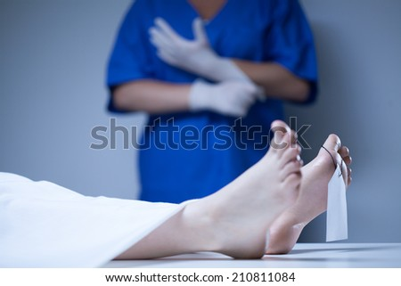 Labeled body of the deceased lying in mortuary - stock photo