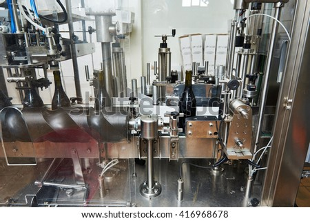 Labeling and sealing conveyor line at winery factory - stock photo