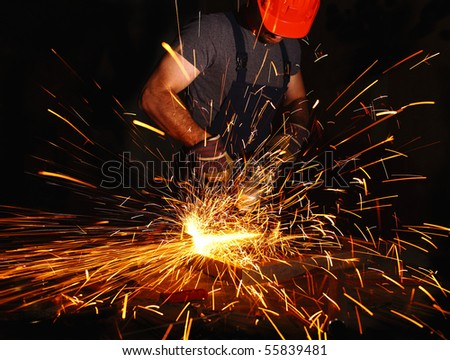 labor aty work with electric grinder, industrial background - stock photo