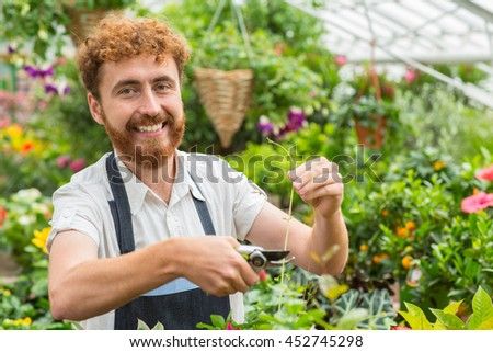 Labor of love. Cheerful smiling male florist trimming potted plants at his nursery smiling to the camera