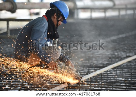 Labor using machine grinding and cutting rebar for ground slab
