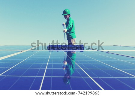 labor working on cleaning solar panel at solar power plant; operation team working on cleaning solar panel