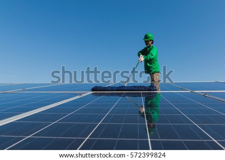labor working on cleaning solar panel with water clean at solar power plant