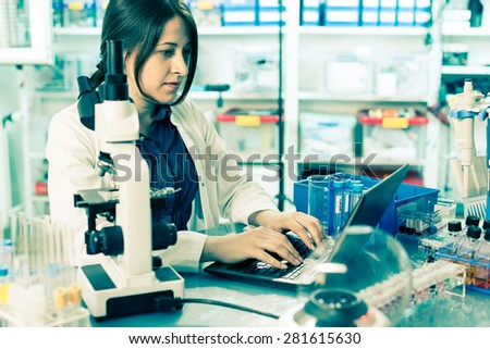 laboratory assistant analyzes of DNA sequence on the computer - stock photo