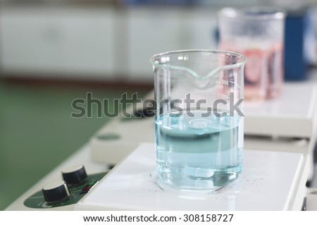 Laboratory equipment. Blue and Pink chemical substance in the beaker. Magnetic stirrer, soft focus