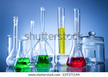 Laboratory equipment, bottles, flasks with color liquid  on blue background - stock photo