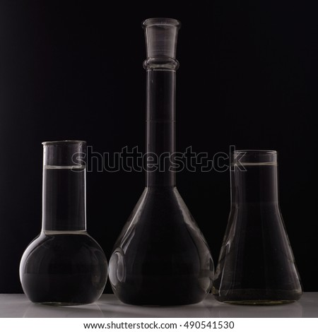 Laboratory equipment, three glass flask on black background.