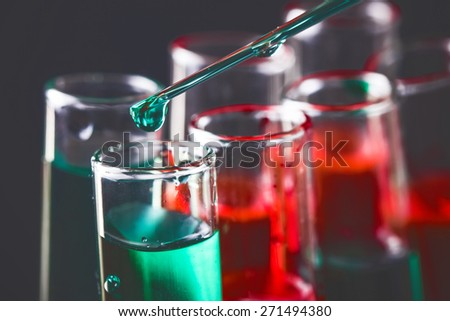 Laboratory flasks with green and red liquid. - stock photo