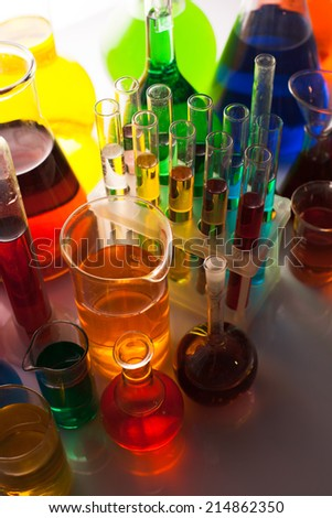 Laboratory glass with rainbow color liquids, chemistry still life - stock photo