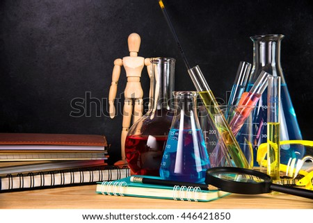 Laboratory glassware containing chemical liquid on wooden table - stock photo