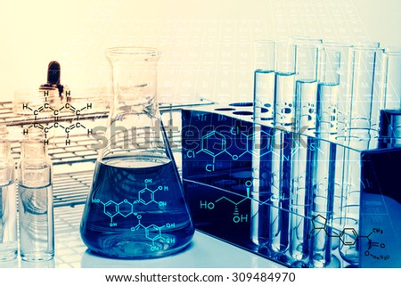 Laboratory glassware containing chemical liquid, science research with chemical equations and periodic table background.
