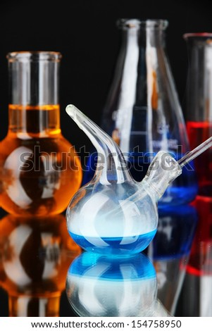Laboratory glassware on black background - stock photo