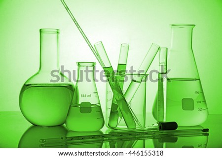 Laboratory glassware on green background