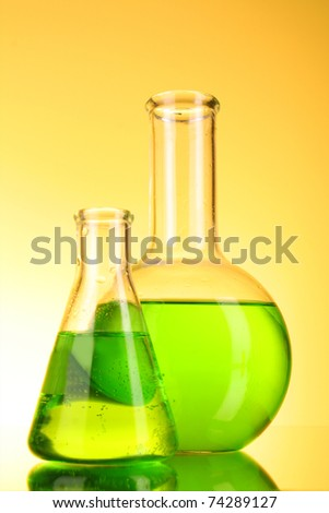 Laboratory glassware on yellow background