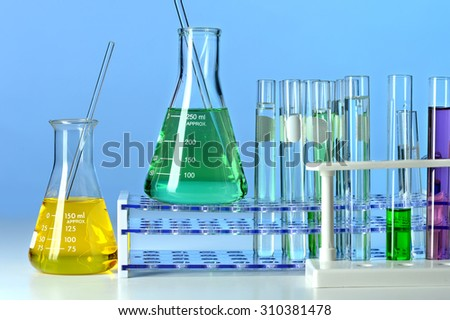Laboratory glassware over table and blue background - stock photo