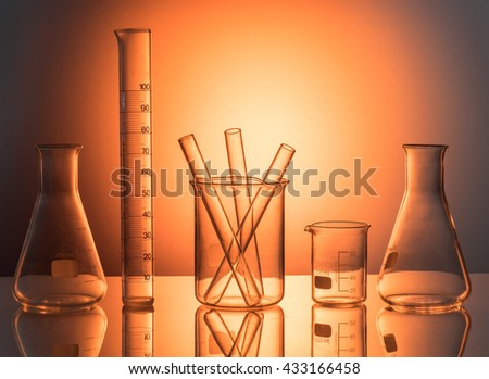 Laboratory glassware still life with colorful reactives toned with yellow filter - stock photo