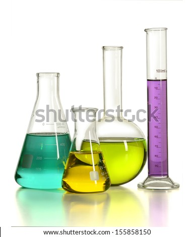 Laboratory glassware with colored liquids over reflective table over white background - stock photo