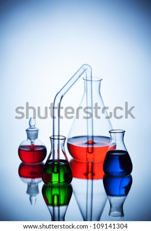 Laboratory glassware with colorful liquids on blue background - stock photo