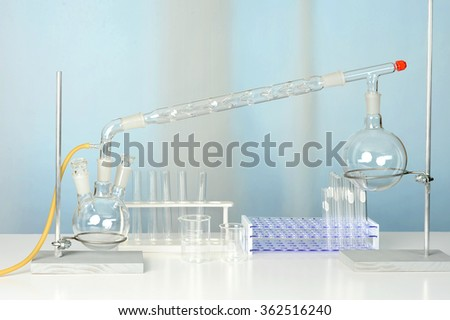Laboratory glassware with distillation set on white table - stock photo