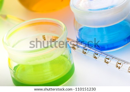 Laboratory glassware with liquids of different colors isolated